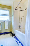 Bright yellow and white bathroom with blue tile floor Royalty Free Stock Photo