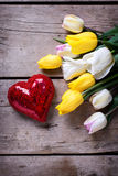 Bright yellow and white spring tulips and shiny decorative heart Stock Photography