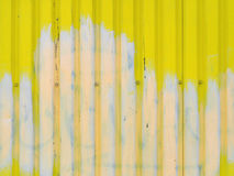 Bright yellow with white stain metal wall background texture with screws in the middle and space for text or image. Stock Photo