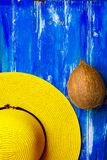 Bright yellow women`s straw hat whole coconut on old painted plank wood blue background. Summer beach vacation stock images