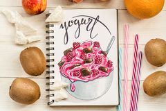A bright yogurt hand-drawn illustration made with markers decorated with fruits and drinking straws on white wooden background royalty free stock image