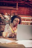 Bright young African girl concernedly looking at laptop screen. Work in cafe. Bright young African girl concernedly looking at laptop screen while sitting in royalty free stock image