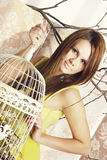 Bright young pretty woman posing with a cage Royalty Free Stock Photos