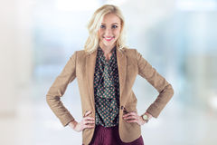 Bright young woman in brown jacket is standing. In office with hands on her hips and smile brightly Royalty Free Stock Image