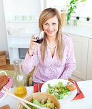 Bright young woman drinking wine and eating salad Royalty Free Stock Image