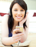 Bright young woman listening to music on the floor Stock Photography