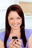 Bright young woman sending a text with her phone Stock Photography