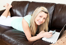 Bright young woman using her laptop on the sofa Stock Image