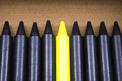 Brightest Crayon in the Box. Expression Brightest crayon in the box represented with eight black crayons and one yellow one Royalty Free Stock Images