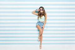 Brightful summer look of joyful young woman with long curly hair, in sunglasses, shorts on heels having fun on striped. Background. Blue colors, expressing royalty free stock image