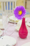 Brightl flower in a vase. Bright artificial flower in a vase on laid table Royalty Free Stock Images