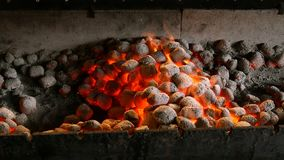 Brightly burning hot briquettes in a brazier. Hot fire flames in a barbecue with glowing and flaming hot charcoal briquettes with red flames stock video