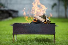Brightly burning in metal box firewood for barbecue outdoor. Camping, safety and tourism concept stock image
