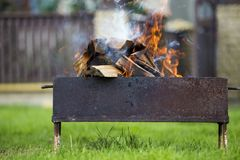 Brightly burning in metal box firewood for barbecue outdoor. Camping, safety and tourism concept stock photography