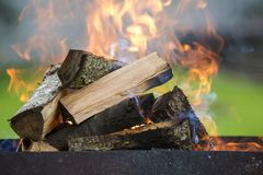 Brightly burning in metal box firewood for barbecue outdoor. Camping, safety and tourism concept royalty free stock photo