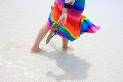 Brightly color on the beach. The girl wearing brightly colored clothes holding sandal walking on the beach Stock Image