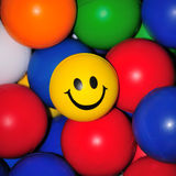 Brightly Colored Balls. Yellow, green, blue, orange, white and red rubber balls with a smiley face in the middle royalty free stock photos