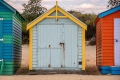 Brightly colored beach huts. Brightly coloured beach huts sitting on the sand with blue skies and clouds Royalty Free Stock Photos