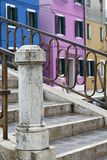 Brightly colored blue, pink and orange, houses with Bridge with metal railings in Burano Venice Italy. Colored blue, pink and orange, houses with Bridge with Stock Photo