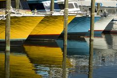 Brightly Colored Boats and Reflections. Bows of several brightly colored boats and reflections in water Stock Photo