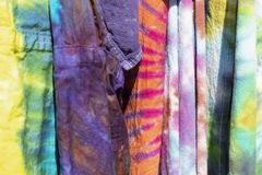 Brightly colored boho tie dyed garments hanging together - background - selective focus.  stock photography
