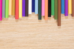 Brightly colored border of pencil crayons. On a wooden background in a concept of art or primary school with copy space below Royalty Free Stock Image