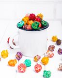 Brightly Colored Candied Popcorn, white background. Horizontal image of Junk food, fruit flavored popcorn in old metal cup. Colorf. Ul, rainbow, candy coated stock image