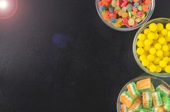 Brightly colored candies in glass cups on a black table, top view Royalty Free Stock Photos