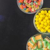 Brightly colored candies in glass cups on a black table, top view Royalty Free Stock Photography