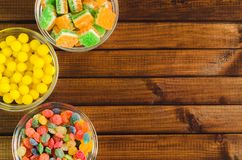 Brightly colored candies in glass cups on a wooden table, top view Royalty Free Stock Image