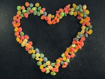 Brightly colored candies are laid out in the shape of a heart on a black background Stock Image