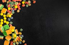 Brightly colored candies on a wooden table with copyspace Stock Images