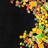 Brightly colored candies on a wooden table with copyspace Royalty Free Stock Photos