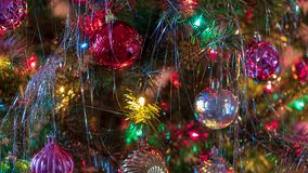 Brightly colored, cheery Christmas tree ornaments hung up with lights and tinsel. Strings royalty free stock photography