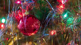 Brightly colored, cheery Christmas tree ornaments hung up with lights and tinsel. Strings stock images