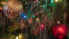 Brightly colored, cheery Christmas tree ornaments hung up with lights and tinsel. Strings royalty free stock photo