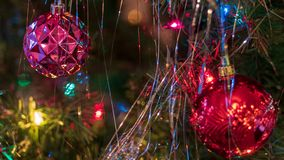 Brightly colored, cheery Christmas tree ornaments hung up with lights and tinsel. Strings stock photo