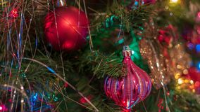Brightly colored, cheery Christmas tree ornaments hung up with lights and tinsel stock photography