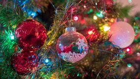 Brightly colored, cheery Christmas tree ornaments hung up with lights and tinsel. Strings stock image