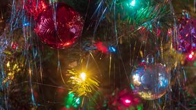 Brightly colored, cheery Christmas tree ornaments hung up with lights and tinsel. Strings royalty free stock photos