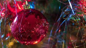 Brightly colored, cheery Christmas tree ornaments hung up with lights and tinsel. Strings royalty free stock image