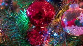 Brightly colored, cheery Christmas tree ornaments hung up with lights and tinsel. Strings stock photography