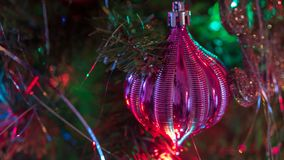Brightly colored, cheery Christmas tree ornaments hung up with lights and tinsel. Strings royalty free stock images