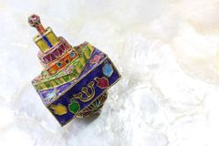 Brightly colored cloisonne Hanukkah dreidel on a soft white background. Horizontal aspect Stock Photography