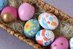Bright colored Easter eggs in a wicker nest, top view stock photos