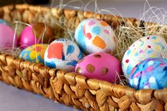 Bright colored Easter eggs in a wicker nest stock images
