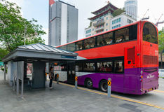 Brightly colored, double decker bus stops, Singapore. Royalty Free Stock Image