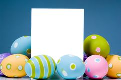 Brightly colored Easter Eggs surrounding white, blank notecard. Brightly colored Easter egg surrounding blank, white notecard with blue background Stock Images