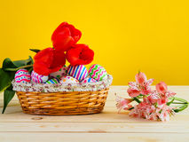 Brightly colored eggs with flowers in a wicker basket Stock Photography