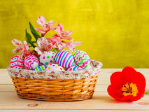 Brightly colored eggs with flowers in a wicker basket Royalty Free Stock Images